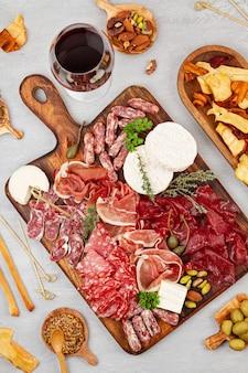 Tavolo da antipasti con diversi antipasti, salumi, stuzzichini e vino. salsiccia, prosciutto, tapas, olive, formaggio e cracker per la festa a buffet. vista dall'alto, piatto