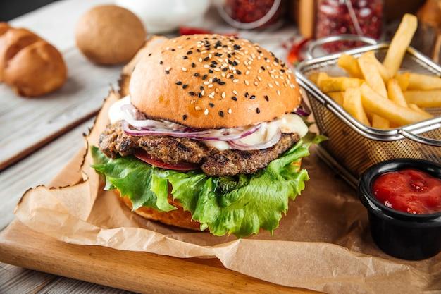 Hamburger americano appetitoso con patatine fritte e salsa