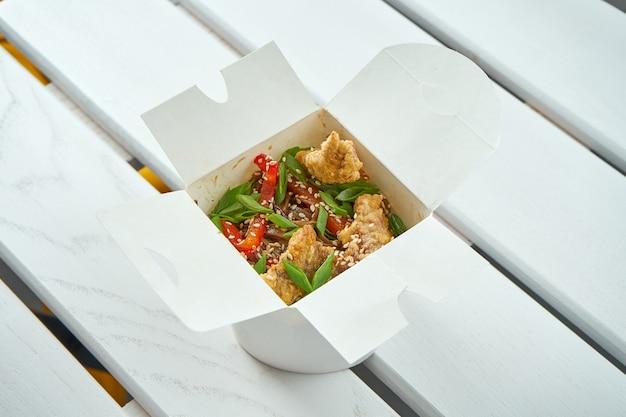 Appetitosi wok asiatici tagliatelle con verdure, cipolle, salse e carne di maiale in una scatola di consegna bianca sul piatto di legno bianco