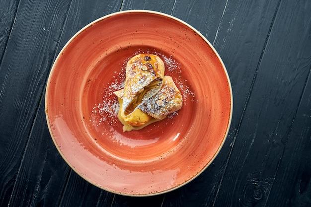 Appetitoso dessert di pasticceria austriaco - strudel di mele con salsa dolce e gelato giallo, servito in un piatto contro una superficie scura.