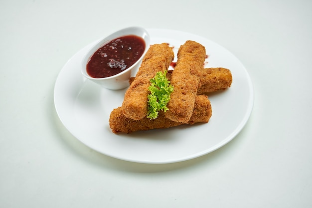 Spuntino appetitoso della birra - bastoncini di formaggio fritti di mozzarella con salsa di mirtilli rossi in un piatto bianco su una superficie bianca