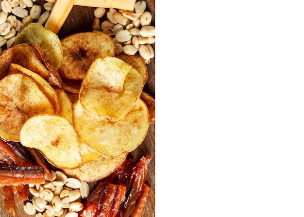 Spuntini appetitosi della birra su un piatto. salsicce fritte, patatine, noci salate e formaggio affumicato. isolato su sfondo bianco. spazio per il testo.