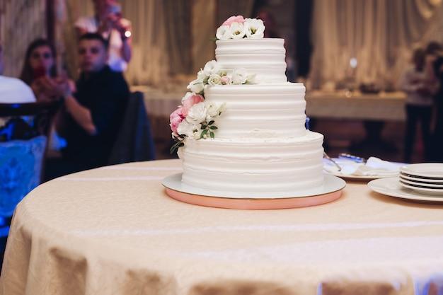 Appetitosa grande torta di pasta fresca ricoperta di glassa di crema bianca e decorare dolce fiore che serve sul tavolo. gustoso evento di matrimonio delizioso dessert pronto per il banchetto alla luce blu illumina lo sfondo