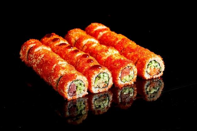 Appetitoso rotolo di sushi californiano incastonato in caviale tobiko con tonno, salmone, anguilla e avocado su sfondo scuro. primo piano, messa a fuoco selettiva