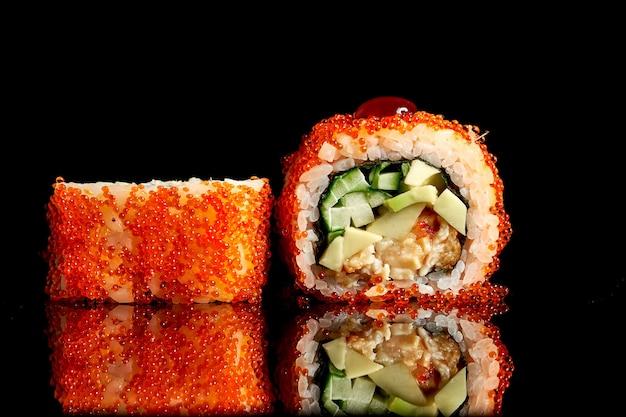 Appetitoso sushi californiano in caviale tobiko con anguilla e avocado su sfondo scuro. primo piano, messa a fuoco selettiva