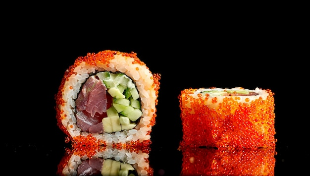 Appetitoso sushi californiano in caviale tobiko con tonno e avocado su sfondo scuro. primo piano, messa a fuoco selettiva