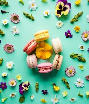 Amaretti colorati appetitosi e bellissimi fiori su sfondo verde. layout piatto
