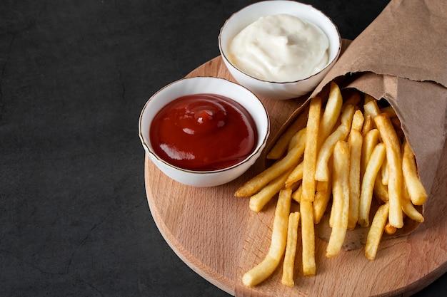 Appetitose patatine fritte croccanti in un sacchetto di carta ecologico su sfondo nero. fast food americano caldo.
