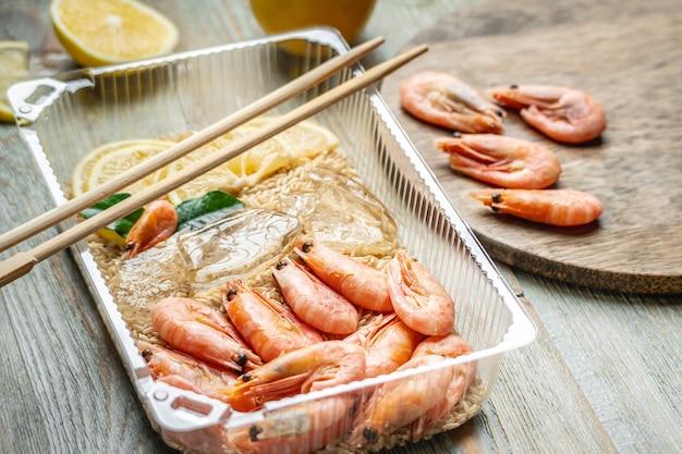 Piatto pronto appetitoso e delizioso di gamberetti e riso in un contenitore di plastica