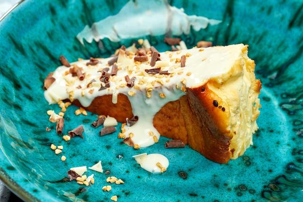 Dessert appetitoso - cheesecake basca con crema pasticcera, scaglie di cioccolato bianco e nero in un piatto blu su sfondo grigio. vista ravvicinata