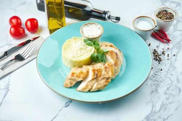 Piatto appetitoso e dietetico - petto di pollo al forno con salsa di formaggio e purè di patate in un piatto blu su una superficie di marmo