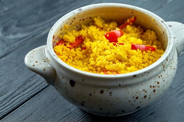 Contorno orientale appetitoso e dietetico - porridge di cuscus con verdure servito in una pentola bianca su fondo di legno nero black