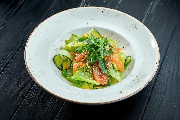 Insalata appetitosa e dietetica con lattuga, cetriolo, avocado e salmone leggermente salato in un piatto bianco su uno sfondo di legno scuro. cibo salutare