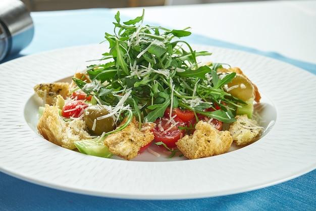 Insalata appetitosa e dietetica con olive, rucola, pomodorini, parmigiano e crostini di pane in un piatto bianco sulla tovaglia blu. avvicinamento