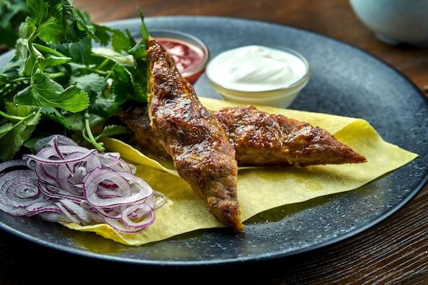 Un piatto appetitoso della cucina turca - kebab di pollo da carne macinata con pane pita, coriandolo, cipolle e salse, servito in un piatto blu su un tavolo di legno. cibo del ristorante. vista ravvicinata