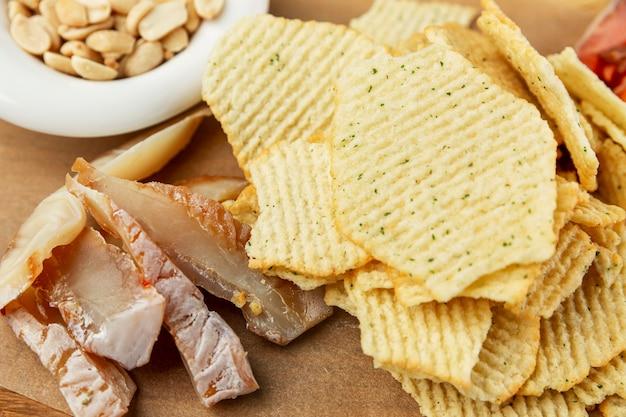 Spuntini secchi appetitosi per la birra. patatine fritte, pesce e noci su una tavola di legno. avvicinamento.