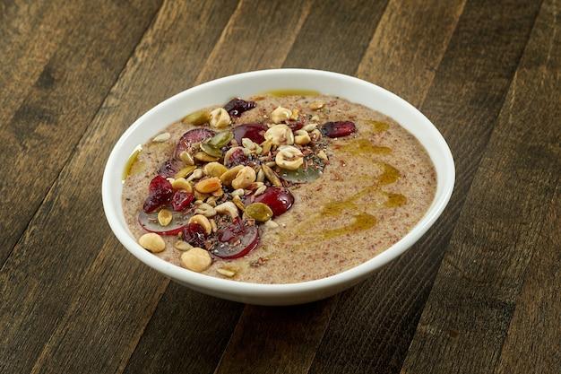 Appetitoso porridge di semi di lino con olio d'oliva, semi, uva e nocciole in una ciotola bianca sul tavolo di legno