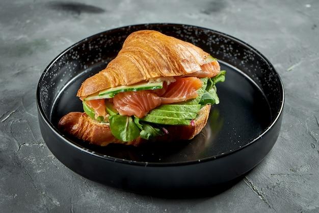 Appetitoso croissant francese sandwich con salmone, avocado, spinaci e salsa, servito in una piastra nera su una superficie grigia