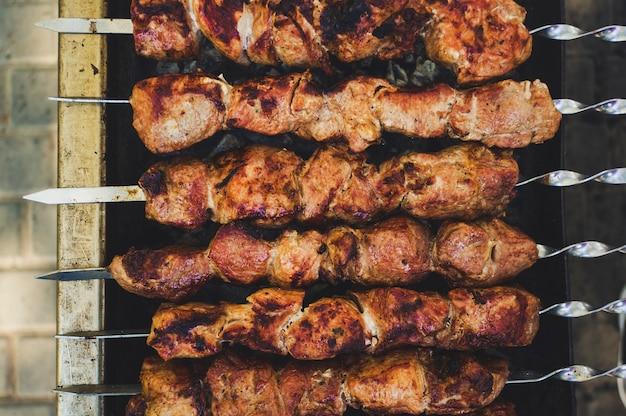 Spiedini di carne fresca appetitosi preparati su una griglia a carbone di legna. vista dall'alto della cottura dello shashlik