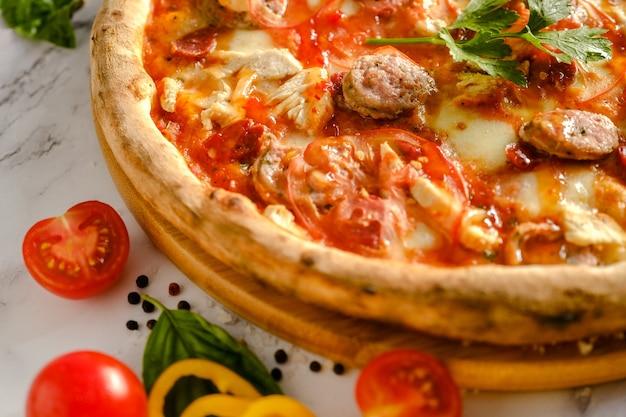 La pizza appetitosa e fresca è sul tavolo. cibo da un ristorante italiano. cucinare la pizza. ingredienti della pizza. cena con amici.