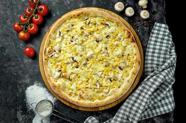 Appetitosa pizza hawaiana con pollo, funghi, mais e ananas in una composizione con ingredienti su una tavola nera
