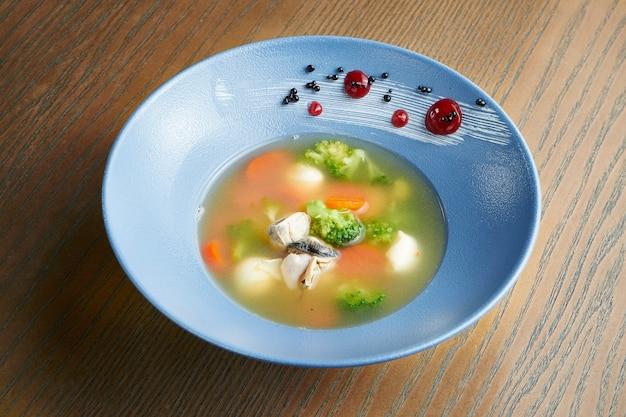Brodo di frutti di mare appetitoso e sano con broccoli, carote, mozzarella e ostriche in una ciotola di ceramica blu su una superficie di legno. effetto pellicola durante la posta. focalizzazione morbida