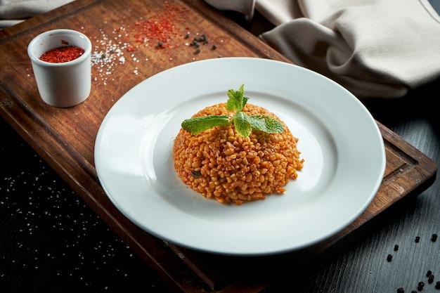 Contorno appetitoso e salutare - bulgur in salsa rossa con spezie turche in un piatto bianco su un tavolo scuro