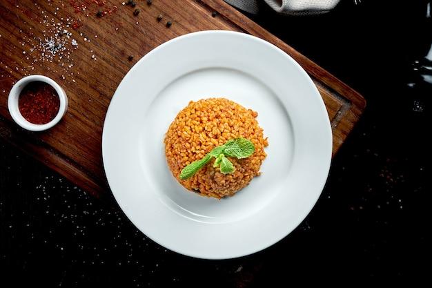 Contorno appetitoso e sano - bulgur in salsa rossa con spezie turche in un piatto bianco su un tavolo scuro