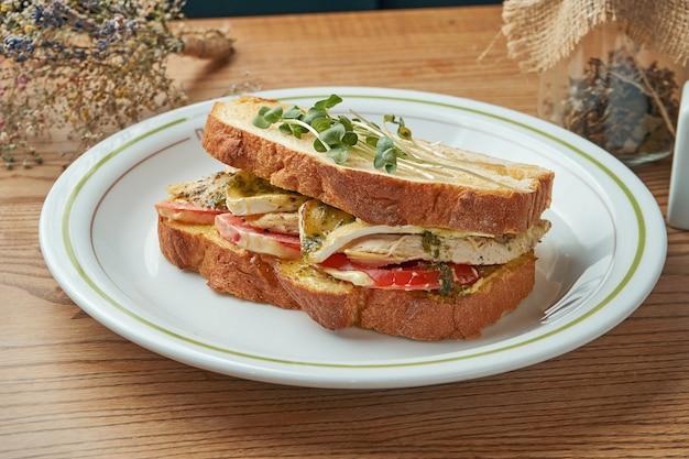 Una colazione appetitosa e abbondante - un panino con pollo, pomodori, salsa bianca e formaggio brie servito in un piatto bianco su un tavolo di legno. cibo del ristorante