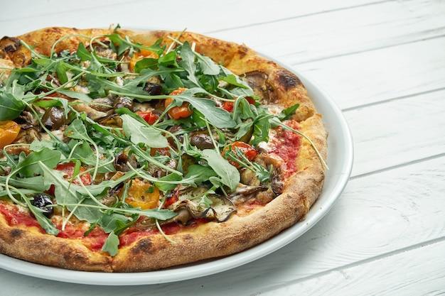 Appetitosa pizza vegetariana fatta in casa con olive, formaggio fuso, rucola, funghi, pomodorini su un bianco