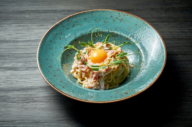 Carbonara di pasta italiana appetitosa con tuorlo, salsa bianca e pancetta in un piatto blu su fondo di legno