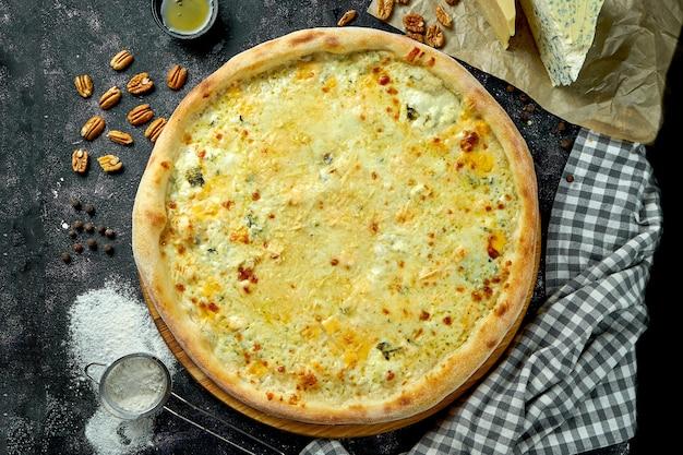 Appetitosa pizza italiana 4 formaggi su una composizione con ingredienti su una tavola nera. vista dall'alto