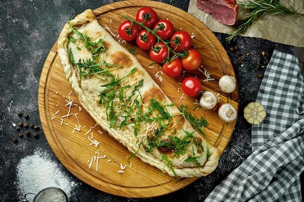 Appetitoso calzone pizza italiana con diversi ripieni in una composizione con ingredienti su una tavola di legno su una tavola nera. vista dall'alto