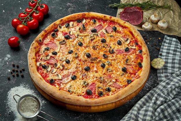 Appetitosa pizza italiana con formaggio, prosciutto, funghi, olive e salsa rossa in una composizione con ingredienti su una tavola nera