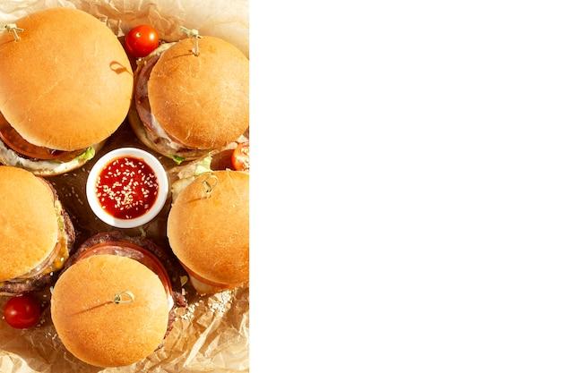 Hamburger succosi appetitosi con salsa su una tavola di legno. cibo spazzatura malsano e gustoso. isolato su sfondo bianco. spazio per il testo. vista dall'alto.
