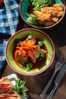 Gulasch di carne appetitoso con salsa (carne e verdure), carote e coriandolo sul tavolo in una splendida cornice, illuminazione solare