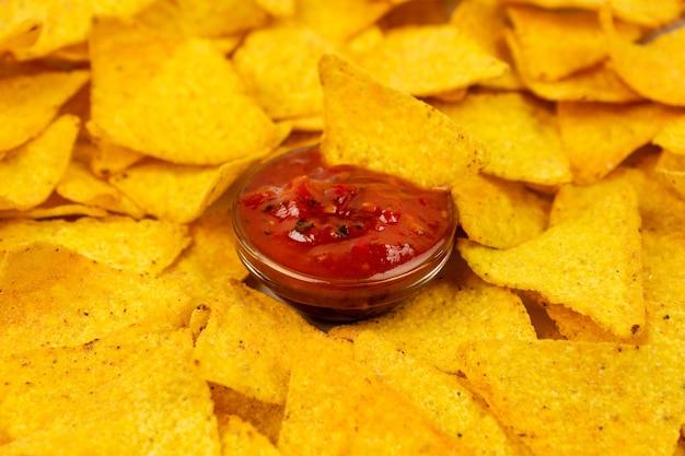 Patatine appetitose dei nachos su un piatto bianco e su un primo piano piccante della salsa. triangoli di tortilla gialli.
