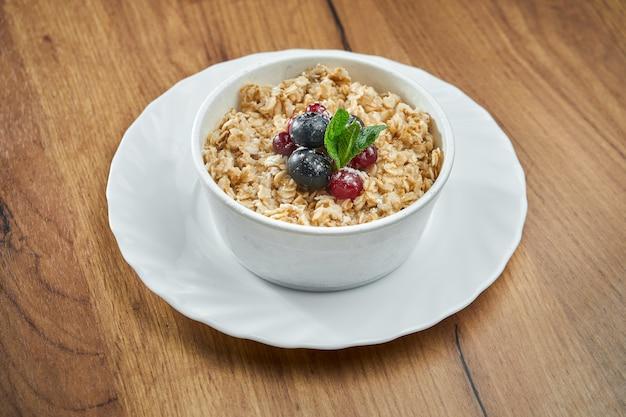 Farina d'avena appetitosa nel latte con i frutti di bosco in una ciotola bianca sulla tavola di legno