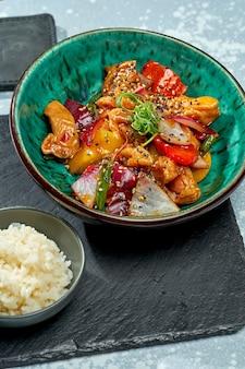 Appetitoso piatto pan-asiatico - wok di pollo in salsa agrodolce con peperone, cipolla, semi di sesamo e contorno di riso in una ciotola blu su sfondo grigio
