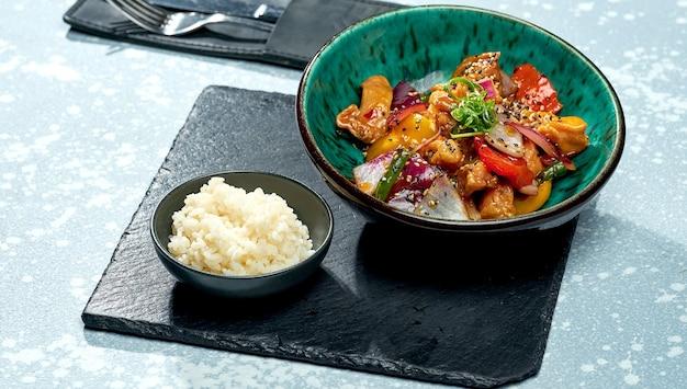 Piatto pan-asiatico appetitoso - wok di pollo in salsa agrodolce con peperone, cipolla, semi di sesamo e contorno di riso in una ciotola blu su una superficie grigia