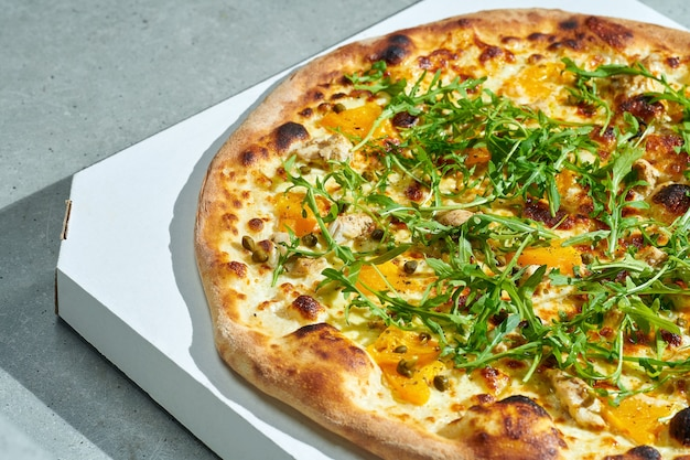 Pizza appetitosa con salsa cremosa, pollo, pomodorini gialli, capperi. lati croccanti. luce forte. superficie grigia.