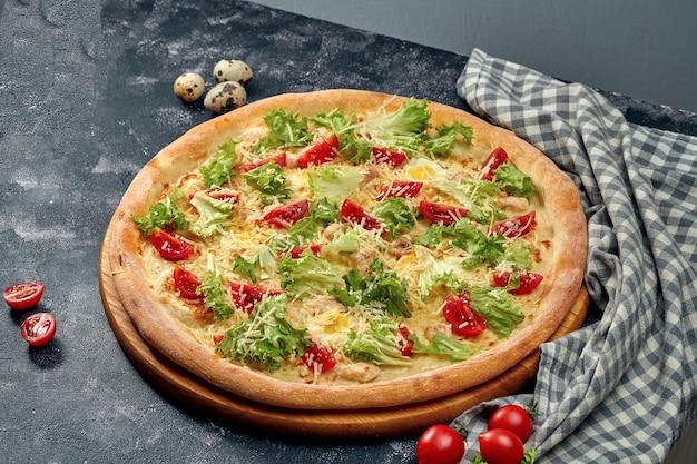Pizza appetitosa con con lattuga, pollo, pomodorini, parmigiano, besciamella. superficie scura. cucina italiana