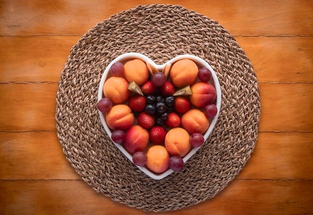 Piatto appetitoso di frutta fresca matura stagionale in un piatto a forma di cuore bianco - mangiare sano con albicocche, uva, fragole, mirtilli e kiwi - fondo in legno