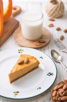 Appetitosa cheesecake di zucca e bicchiere di latte, mandorle