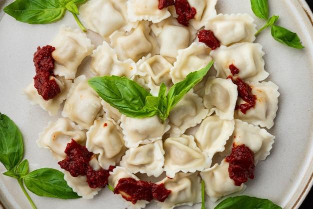 Ravioli appetitosi con salsa di pomodoro, formaggio e basilico con parmigiano e pomodoro basilico sulla piastra bianca sul vecchio tavolo in legno scuro, vista dall'alto piatto
