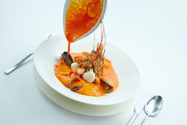 Appetitosa zuppa bouillabaisse rossa viene versata da una ciotola con salmone, capesante, scampi e cozze, servita in un piatto bianco sulla tovaglia bianca