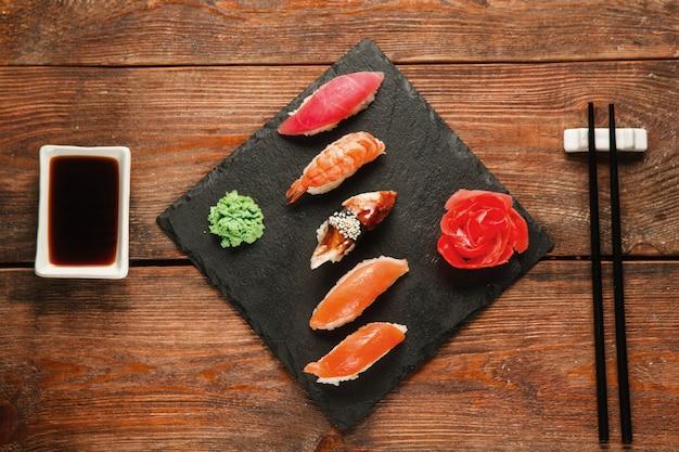 Appetitoso set di cinque nigiri sushi servito su ardesia nera con zenzero e wasabi, su un tavolo rustico in legno, piatto. cucina tradizionale giapponese, pesce sano e gustoso.