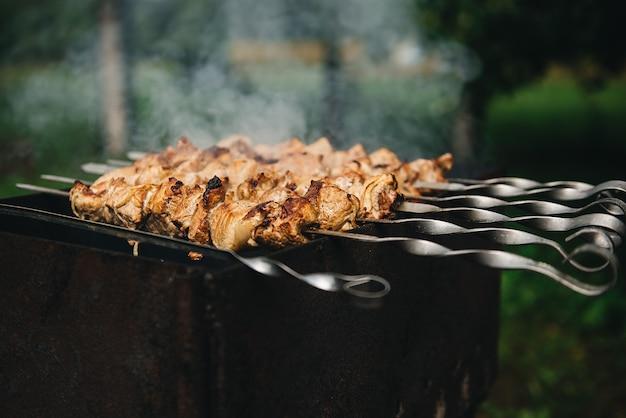 Kebab appetitoso arrostito su spiedini su griglia a carbone all'aperto. shish kebab con fumo