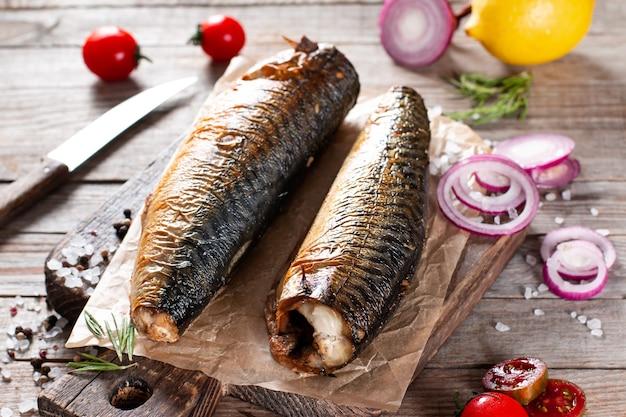Sgombro affumicato appetitoso del pesce, sul vecchio fondo di legno scuro della tavola