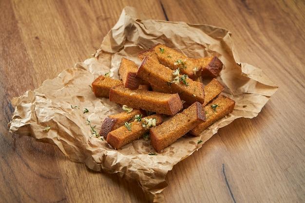 Spuntino appetitoso con birra - crostini di segale con aglio ed erbe aromatiche su pergamena su una superficie di legno.